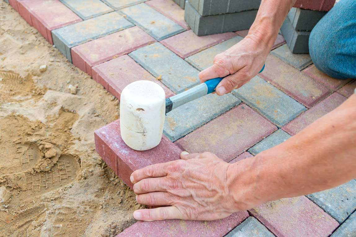 landscaper laying bricks