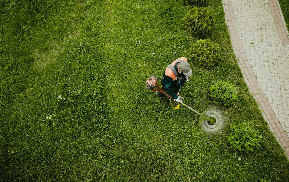 man using lawn mower on grass